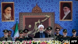 """A handout picture provided by the Iranian presidency on September 22, 2019 shows President Hassan Rouhani (C) giving a speech during the annual """"Sacred Defence Week"""" military parade marking the anniversary of the outbreak of the devastating 1980-1988 war"""