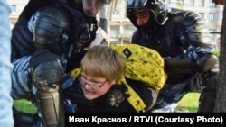 A 14-old year boy is roughly detained by police in Moscow during an antigovernment protest earlier this year.