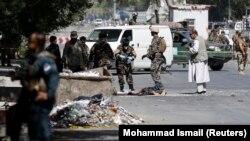 Сотрудники сил безопасности Афганистана на месте атаки в Кабуле. 23 июля 2016 года.