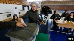 A woman casts her vote at a voting center in Pristina on December 1.