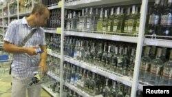 Молодой человек выбирает алкогольные напитки в супермаркете. Киев, 22 мая 2012 года.