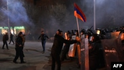 Armenia -- A man is holding an Armenian flag up as protesters clash with police during a demonstration near the Russian Consulate in Gyumri, January 15, 2015