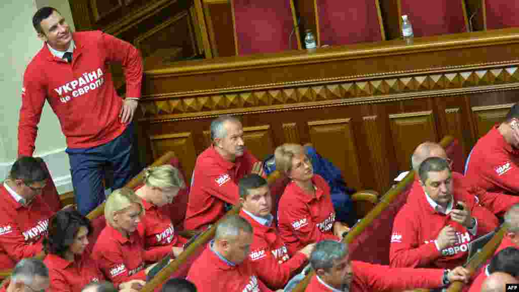 """Ukrainian boxer and opposition party leader Vitali Klitschko smiles as he and his deputies wear """"Ukraine is Europe"""" T-shirts during the opening of the new parliamentary session in Kyiv. (AFP/Sergei Supinsky)"""