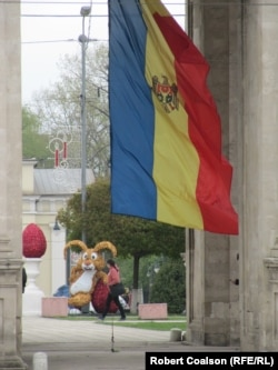 A woman walks past an Easter bunny adorning Chisinau's Cathedral Park.