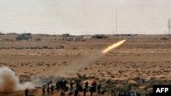 Лібійскія паўстанцы страляюць па пазыцыях войскаў Кадафі ў некалькіх кілямэтрах каля Рас-Лануфа. 9 сакавіка 2011 г.