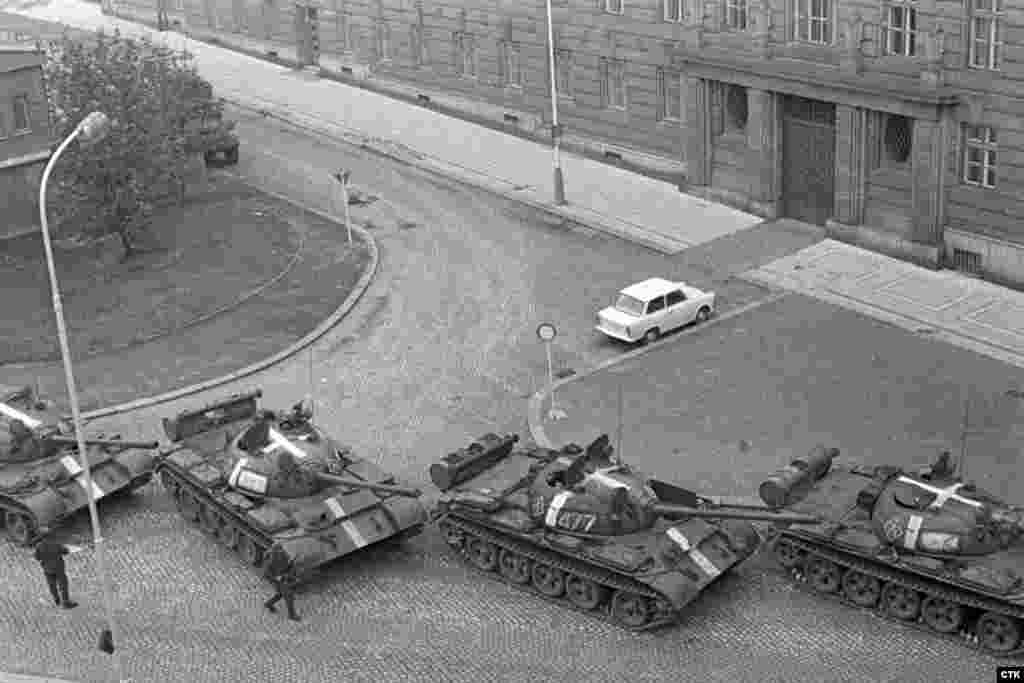 Invading Soviet tanks with white markings deploy near the Communist Party headquarters in Prague.