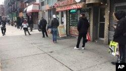Люди сНью-Йорктің Trader Joe's супермаркетіне келгендер ара қашықтық сақтап, кезекте тұр.