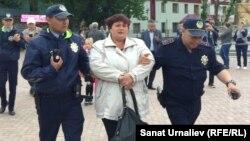 Мәншүк Мәметованың ескерткішін сүруге қарсылық танытқан Оксана Терновскаяны полиция ұстап әкетіп барады. Орал, 22 мамыр 2017 жыл.