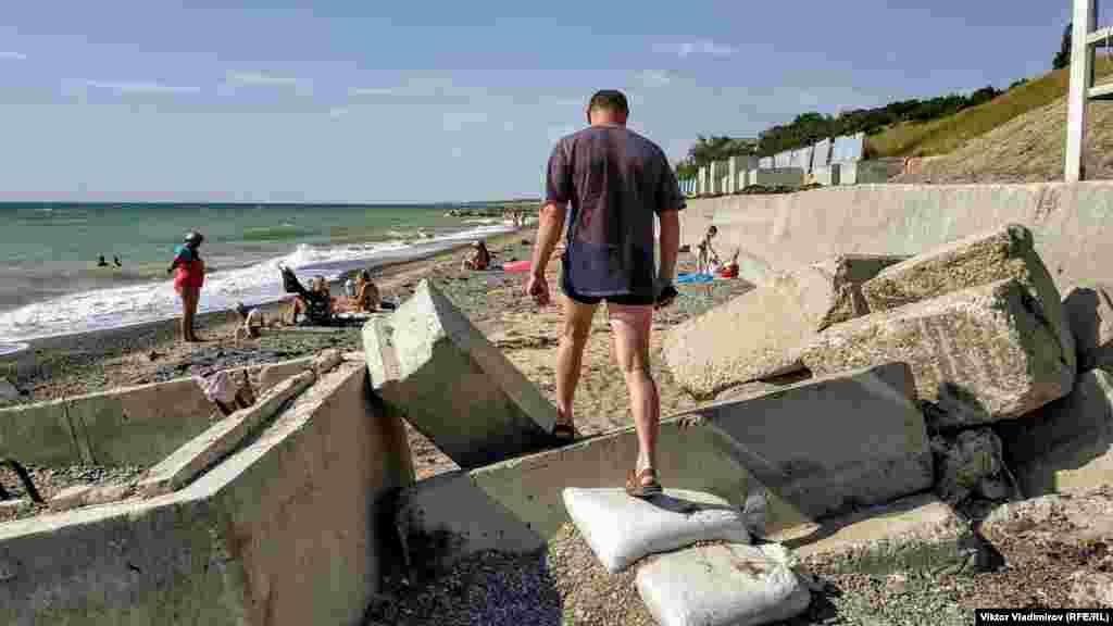 Щоб потрапити на пляж, потрібно подолати зруйновані берегові споруди