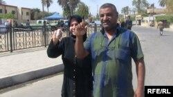 رجل وإمرأة يلوحان بإصبعيهما البنفسجيين بعد الإدلاء بصوتيهما في مركز إقتراع ببغداد