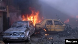 Syria -- Cars burn after two car bombs at Karm al-Louz neighbourhood in Homs city, April 9, 2014, in this handout released by Syria's national news agency SANA.