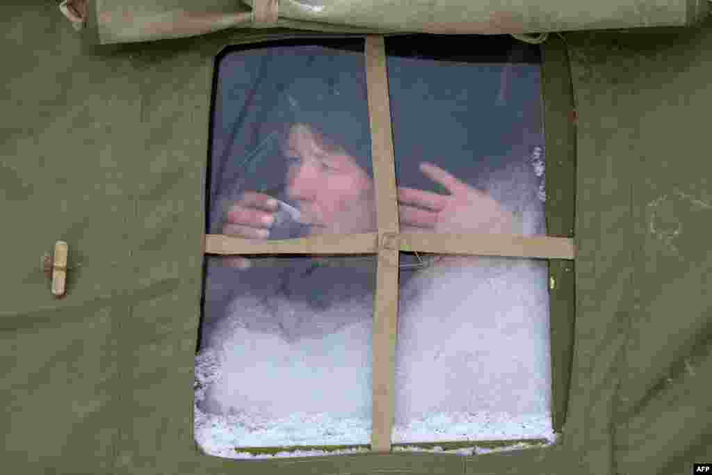 A homeless woman drinks free tea in a tent set by Ukraine's Emergencies Ministry in the city of Donetsk.