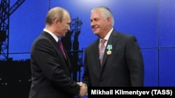 Russian president Vladimir Putin (left) and ExxonMobil Chairman and CEO Rex Tillerson shake hands at an energy summit in St. Petresburg in June 2013.