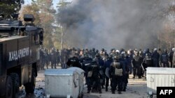Bulgarian riot police stand by during clashes in the migrant reception center at Harmanli on November 24 after 1,500 migrants started rioting and setting fires at the country's largest refugee camp.