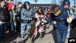 Police intervene against two young protesters at an anticorruption rally in central Moscow on March 26.