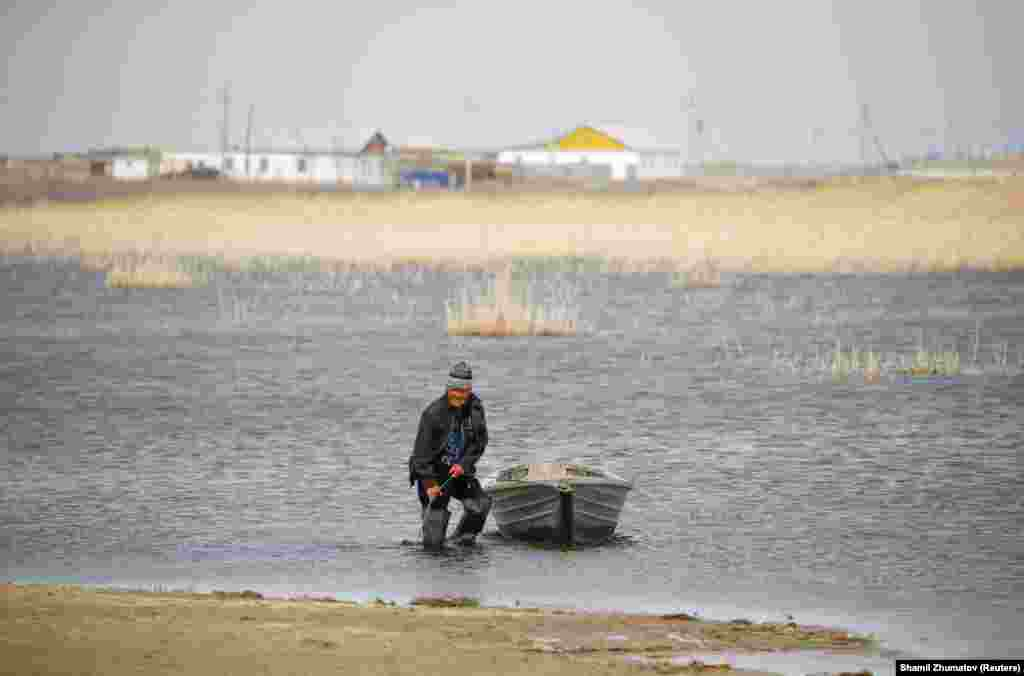 Қаратерең ауылының тұрғыны қайығын теңіз жағасына шығарып жатыр.