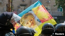 Ukrainian riot police block opposition supporters carrying a flag with the portrait of jailed former Prime Minister Yulia Tymoshenko from entering the city hall during a rally in Kyiv in July.