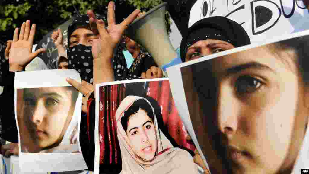 Islamist activists in Lahore carry photographs of Malala during a protest against the assassination attempt.