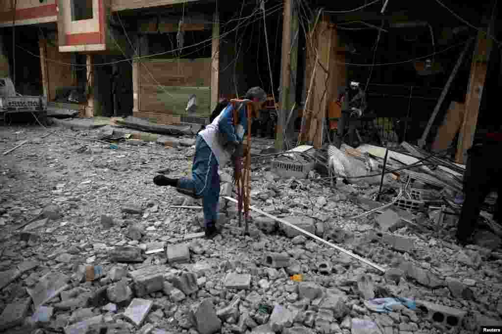 Мужчины в сирийском городе Дума, близ Дамаска, пытаются найти свои вещи после ракетного обстрела их квартала.