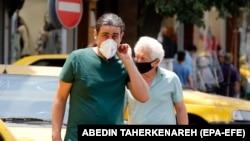 Люди в масках на улице в Тегеране. 5 июля 2020 года.