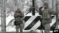 U.S. troops guard the main access checkpoint to the Manas air base.
