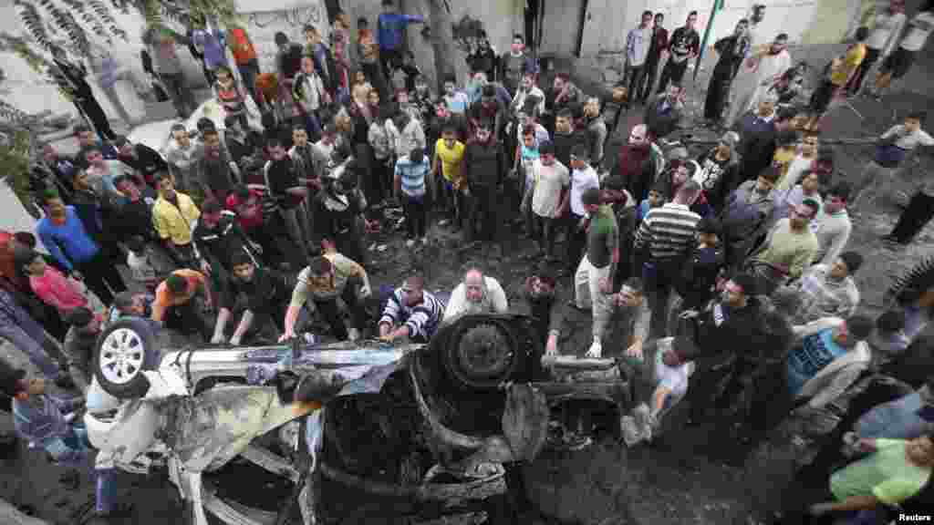Palestinians gather around a destroyed car after an Israeli air strike in Gaza City. (Reuters/Ali Hassan)