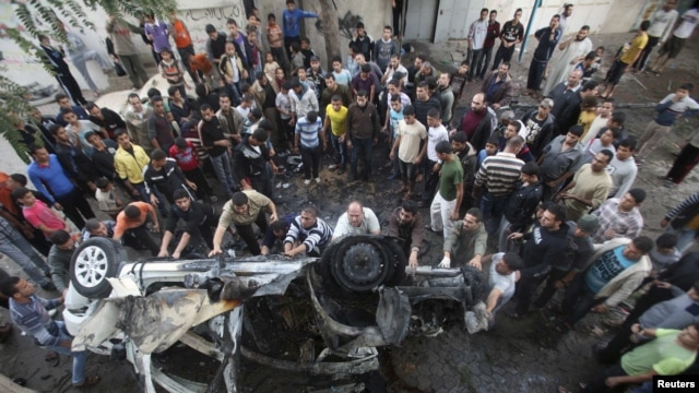 Palestinians gather around a destroyed car after what witnesses said was an Israeli air strike in Gaza City on November 20.