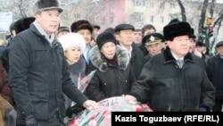 Серикжан Мамбеталин в бытность лидером партии «Руханият» (слева) вместе с писателем Мухтаром Шахановым (справа) перед возложением цветов к памятнику жертвам Декабрьских событий 1986 года. Алматы, 17 декабря 2011 года.