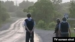 Police stand guard during the manhunt in the Primorsky region.