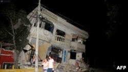 Жители ходят по улице на фоне разрушенных зданий после землетрясения в Эквадоре. 16 апреля 2016 года.