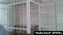 A barred cell in a Tajik courtroom