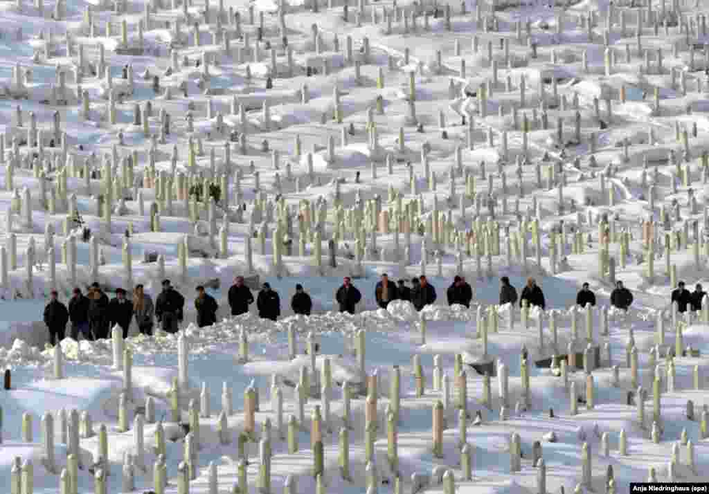 Sarajevans cross the Bare cemetery outside the Bosnian capital on January 27, 2000.