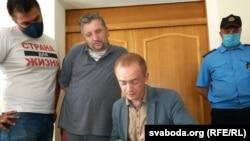 Яўген Васількоў (другі зьлева, у шэрай кашулі) з адвакатам у судзе