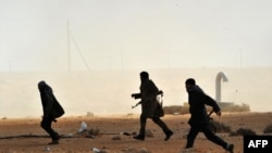 Libyan rebel fighters run to give assistance to their comrades after a Qaddafi air strike east of Ras Lanuf