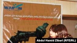 إمرأتان تجلسان أمام ملصق كبير يدين إنتشار الأسلحة في كردستان