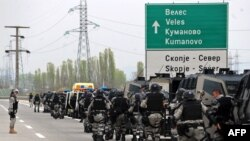 Policemen leave their vehicles to block the road on April 13, one day after news that five dead bodies were found by a local fisherman near the village of Smiljkovci.