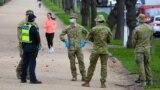 Policijski službenici i vojnici patroliraju popularnom stazom za trčanje u Melburnu 4. avgusta 2020. nakon što je država najavila nova ograničenja jer se grad bori protiv porasta oboljelih od COVID-19.
