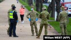 Policijski službenici i vojnici patroliraju popularnom stazom za trčanje u Melburnu 4. avgusta 2020.