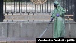 Специалист в защитном костюме проводит дезинфекцию тротуара в центре Бишкека. 26 марта 2020 года.