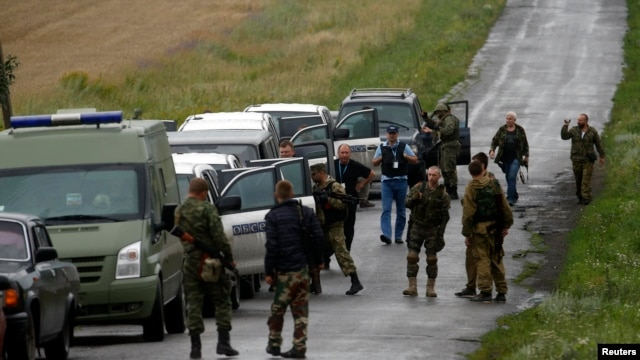 Pro-Russian separatists watch as OSCE  monitors arrive at the crash site on July 18