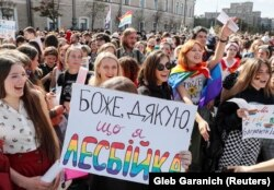 Demonstrators at the Kharkiv gay-pride march hold a sign saying Thank God I'm a Lesbian. Some 2,000 people attended the event.