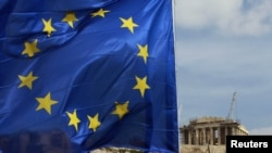 A European Union flag flies in front of the Parthenon temple in Athens