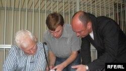 Алесь Бяляцкі, Уладзімер Лабковіч, Валянцін Стэфановіч знаёмяцца з матэрыяламі справы ў залі суду ў час перапынку