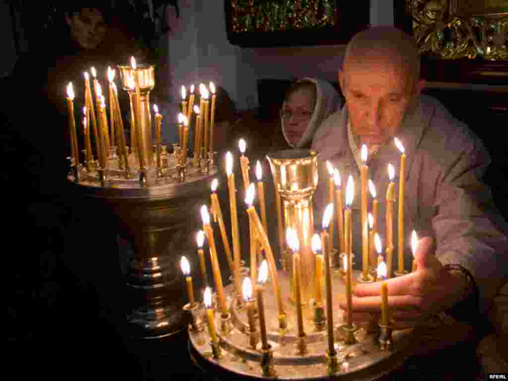 Believers light candles at the St. Peter Cathedral in Minsk, Belarus.