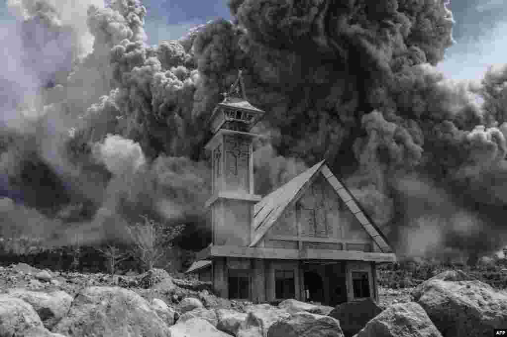 Ash from the Mt. Sinabung volcano fills the sky over an abandoned church during another eruption in Karo, in Indonesia's North Sumatra Province. (AFP/Sutanta Aditya)
