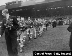 Dynamo Moscow players walk out onto the pitch at Stamford Bridge carrying bouquets for their Chelsea opponents.