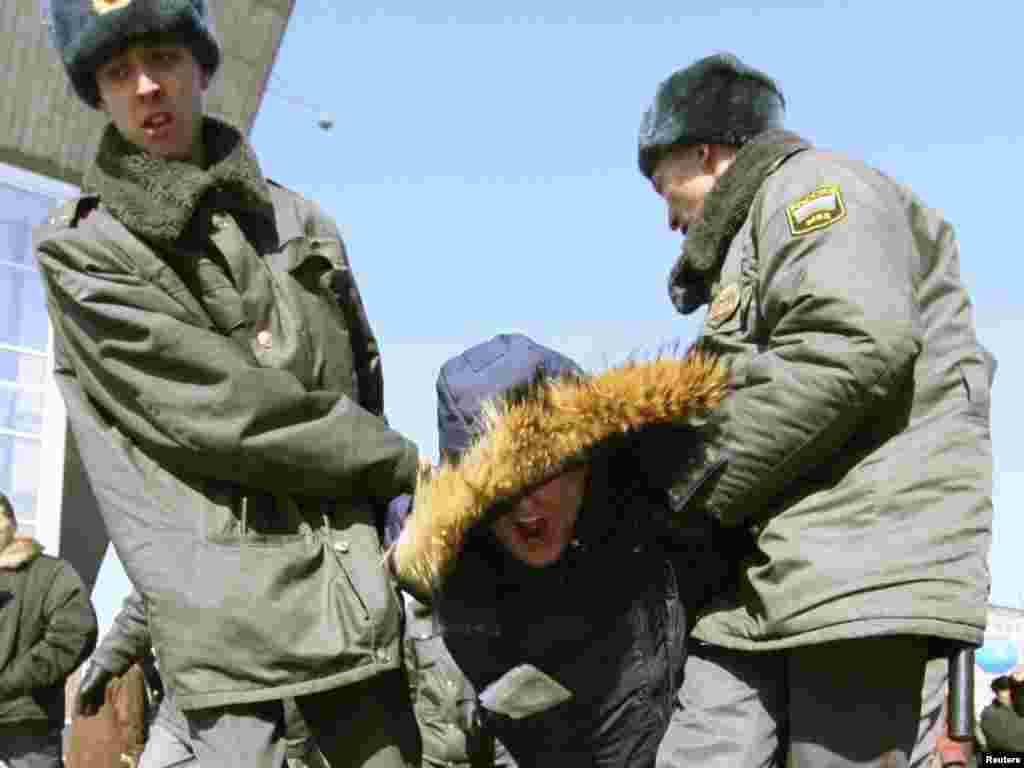 Police detain an opposition supporter in Irkutsk.
