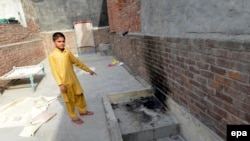 A local resident shows the place where Zeenat Rafiq was allegedly burnt alive by her mother in the eastern Pakistani city of Lahore on June 8.