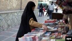 Тегеран көшесінде газет-журнал сататын жерде тұрған әйел. (Көрнекі сурет.)