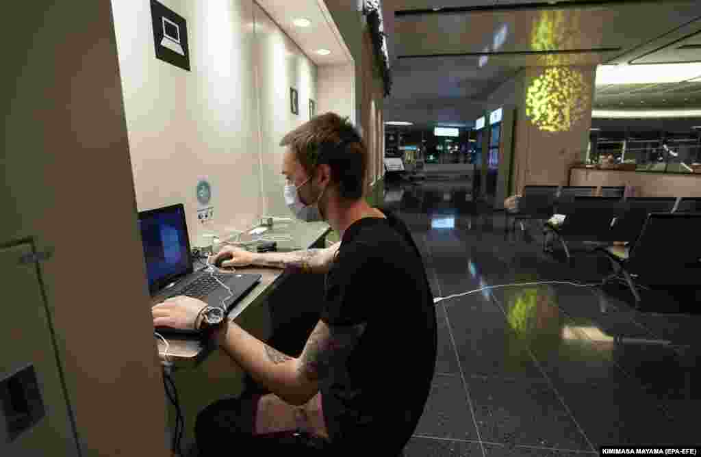 A Russian man wearing a protective face mask looks at his laptop at Tokyo International Airport on April 14.